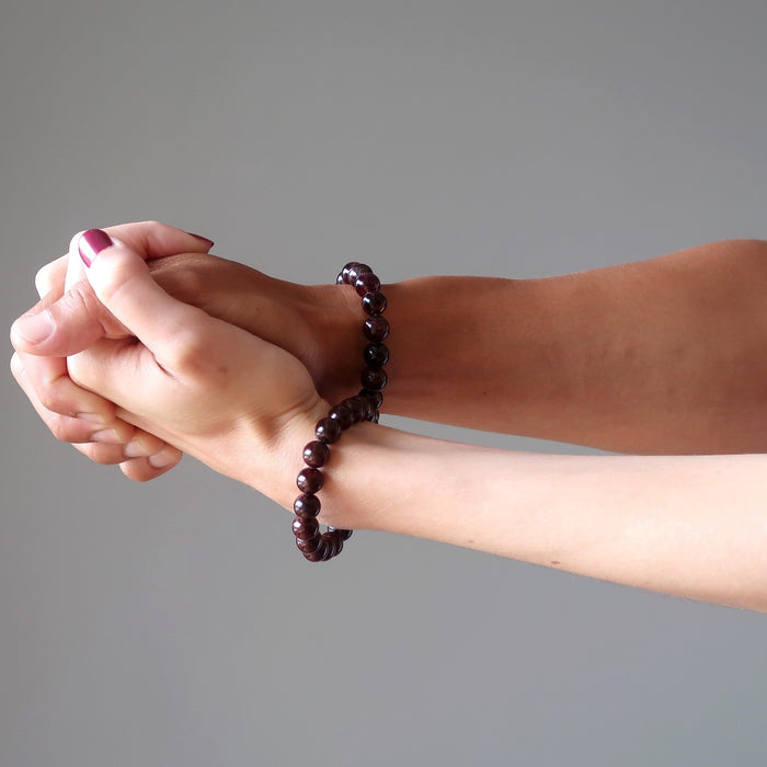 man and woman holding hands wearing red garnet bracelets