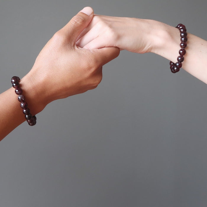 male and female hands wearing red garnet bracelets