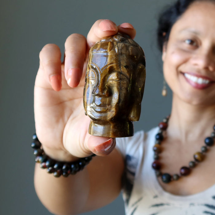 sheila of satin crystals holding golden brown tigers eye buddha head