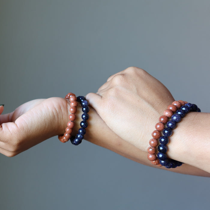 female hands wearing goldstone bracelet sets