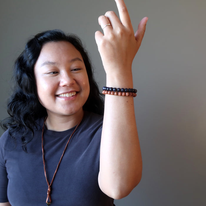 jessica of satin crystals admiring the goldstone bracelet set on her raised hand