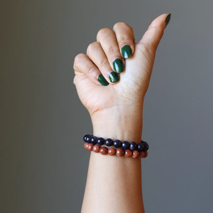 female hand making a thumbs up wearing blue and brown goldstone bracelet set