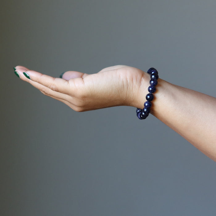 female hand wearing blue goldstone bracelet