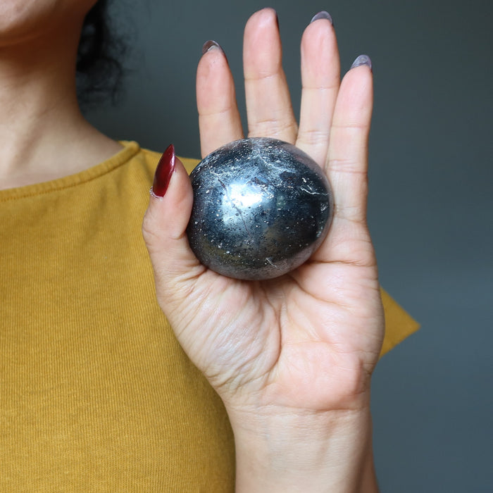 hematite sphere in palm of hand