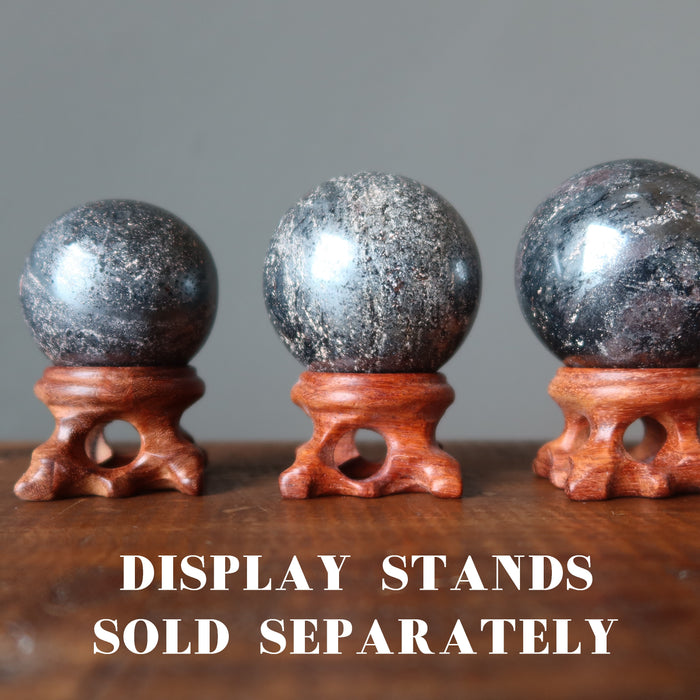 three hematite spheres on wood ball stands, which are sold separately