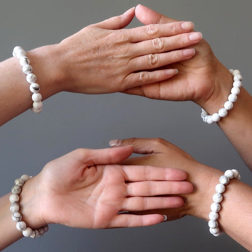 four hands all wearing howlite stretch bracelets