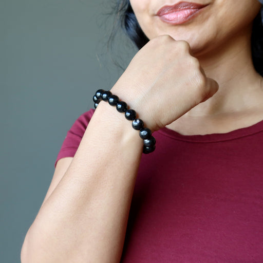 female with hand on chin modeling hypersthene bracelet