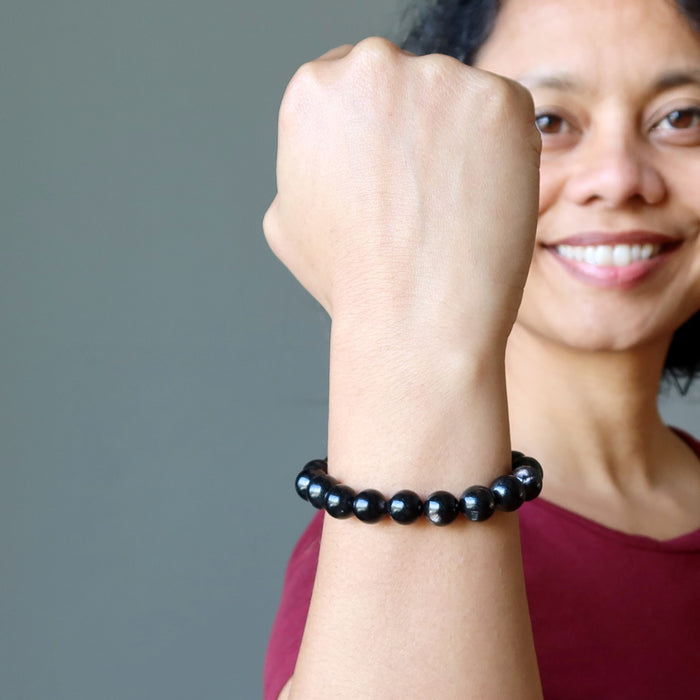 sheila of satin crystals with fist up wearing hypersthene bracelet
