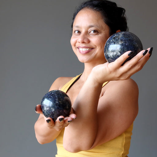 sheila of satin crystals holding two iolite spheres