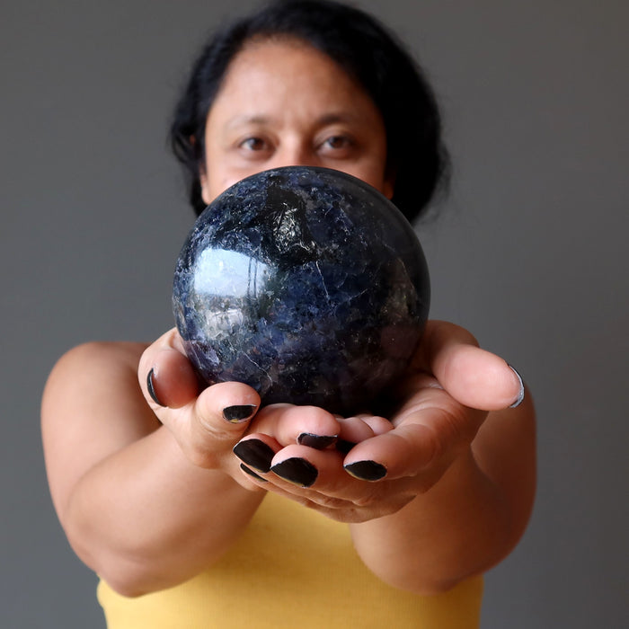 sheila of satin crystals holding an iolite sphere