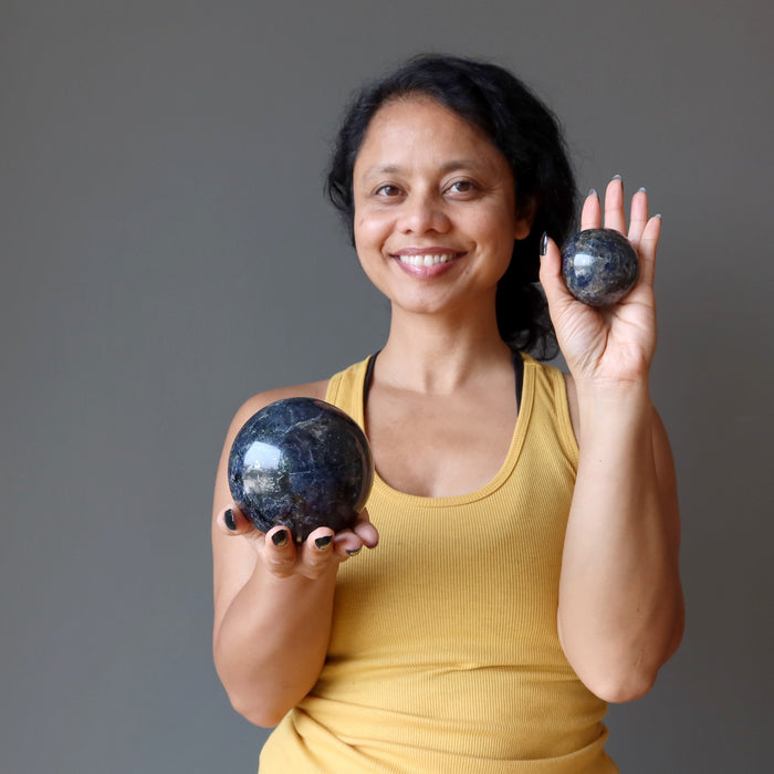 sheila of satin crystals holding two iolite spheres to show size difference