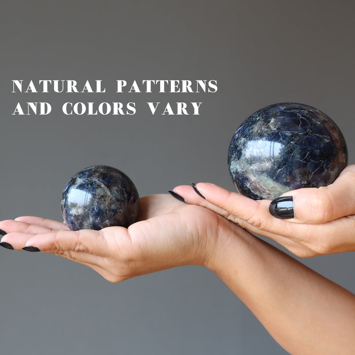 two hands holding iolite spheres in each palm showing natural patterns and colors vary