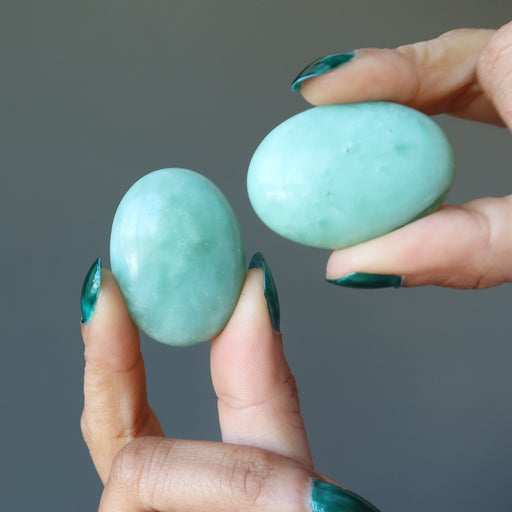 hands holding pair of green jade oval cabochons