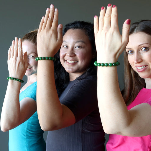 3 female models with hands up wearing bright green jade round beaded bracelets