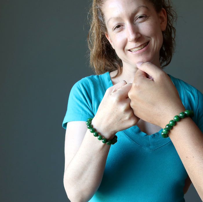 jamie of satin crystals fist pumping female hand both wearing bright green jade round beaded bracelets