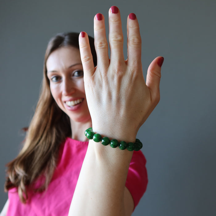 holly of satin crystals with hand up wearing bright green jade round beaded bracelet