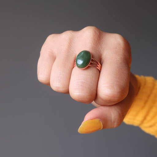 fist wearing green jade oval in copper adjustable ring