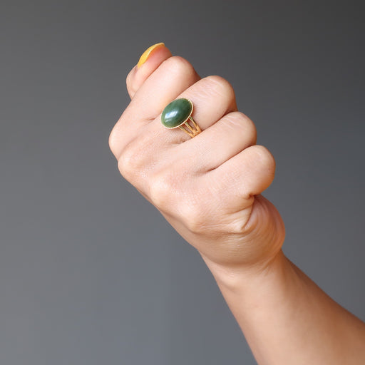 hand making a fist wearing nephrite jade oval in gold adjustable ring