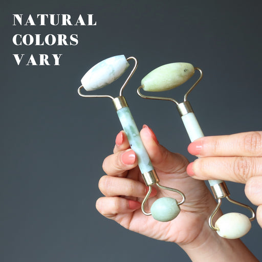 hand holding two jade rollers to show natural colors vary