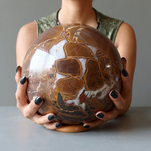 hands on large brown and white snake jasper sphere