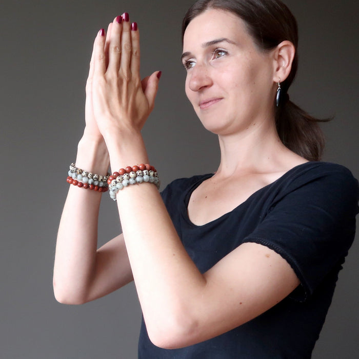 lucia of satin crystals with hands in prayer wearing set of 3 sesame, red and dalmatian jasper stretch bracelets on each hand.