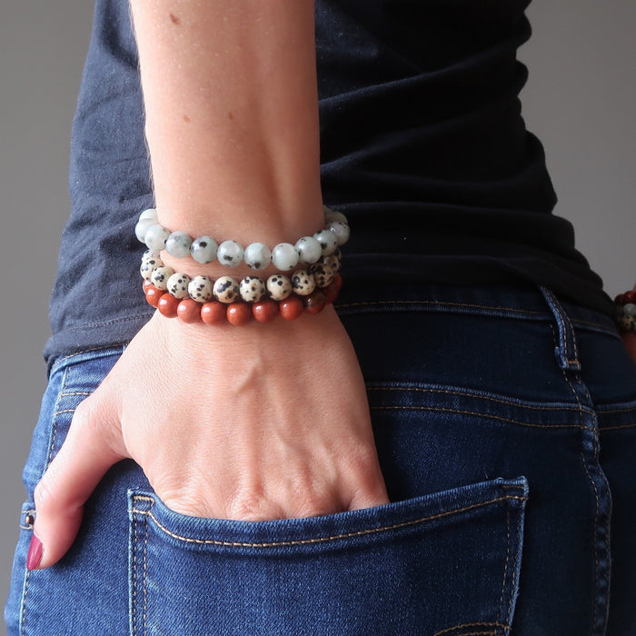 lucia of satin crystals with hands in back jean pockets, wearing set of 3 sesame, red and dalmatian jasper stretch bracelets on each hand.