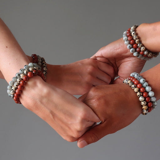 4 hands holding each other all wearing stackable jasper medley bracelets