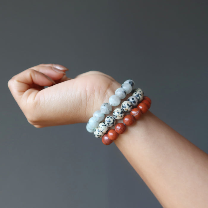 hand  wearing set of 3 sesame, red and dalmatian jasper stretch bracelets.