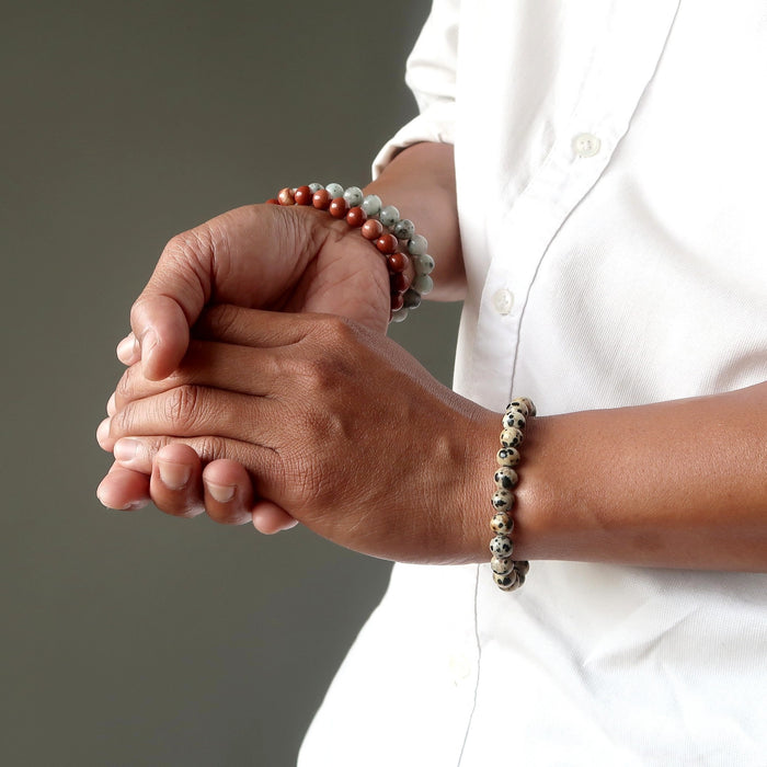 man's hands wearing sesame and red jasper bracelets on one hand and a dalmatian jasper bracelet on the other