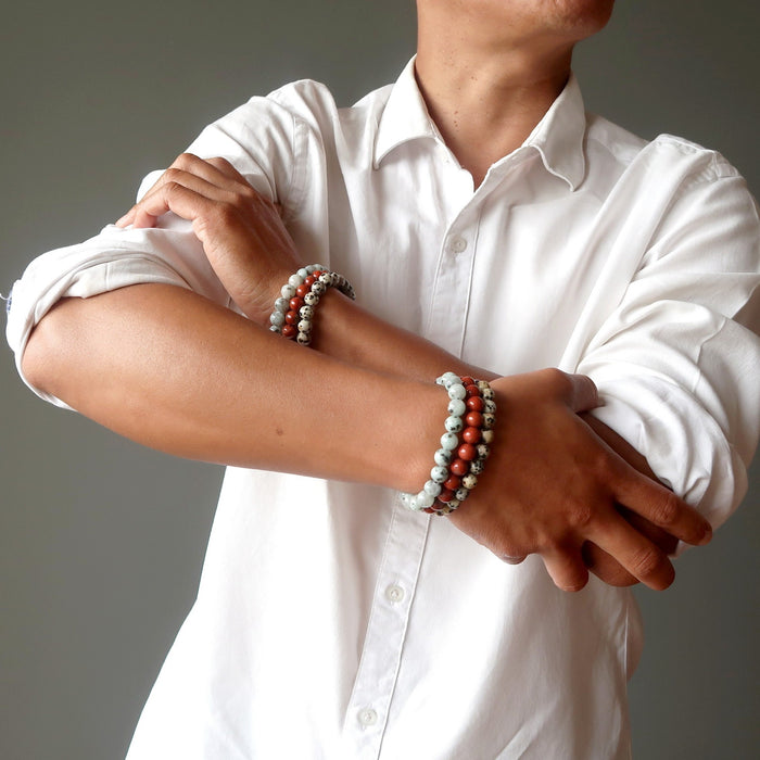 man with arms crossed wearing set of 3 sesame, red and dalmatian jasper stretch bracelets on each hand.