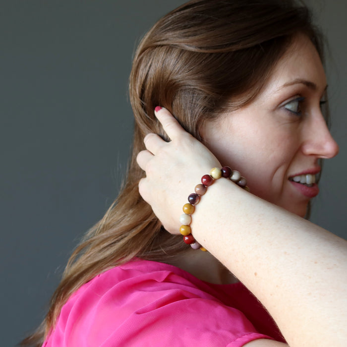 holly of satin crystals with hand in hair wearing multi colored mookaite jasper round beaded stretch bracelet