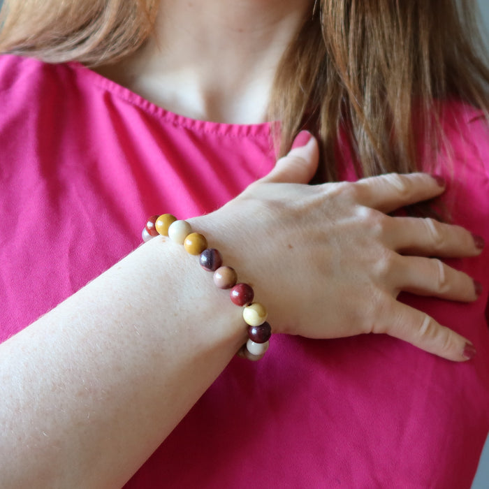holly of satin crystals with hand on heart wearing multi colored mookaite jasper round beaded stretch bracelet