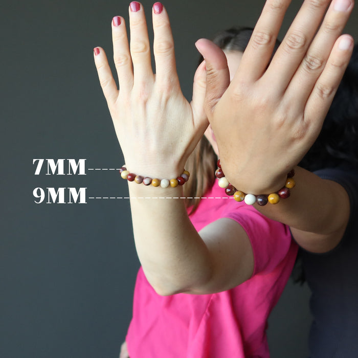 two women with hands out wearing multi colored mookaite jasper round beaded stretch bracelets in 7mm and 9mm