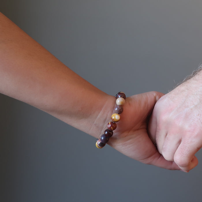 couple holding hands wearing multi colored mookaite jasper round beaded stretch bracelet