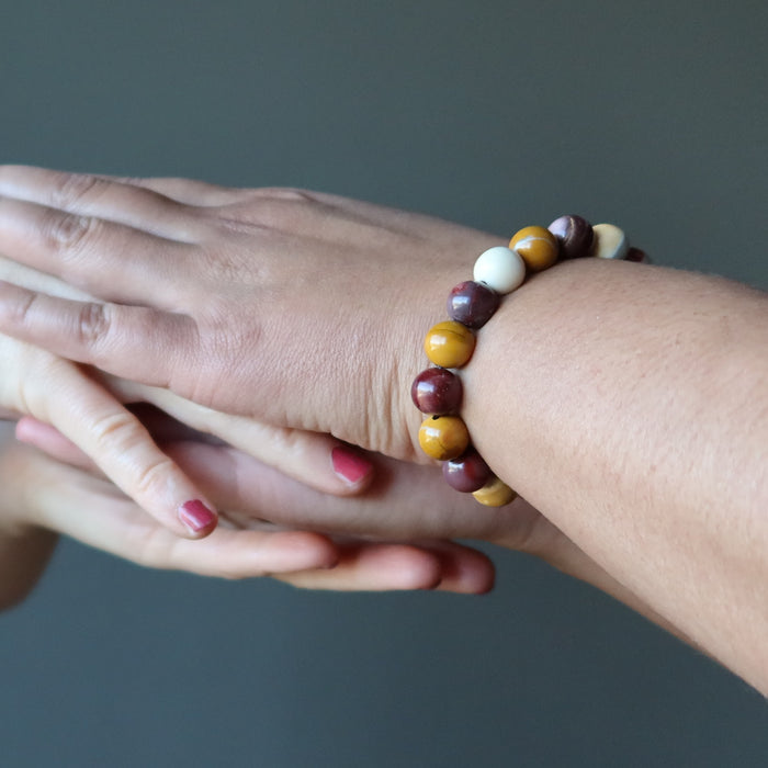 stacked hands wearing multi colored mookaite jasper round beaded stretch bracelet