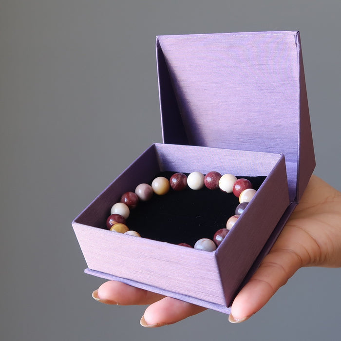 hand holding purple gift box with multi colored mookaite jasper round beaded stretch bracelet