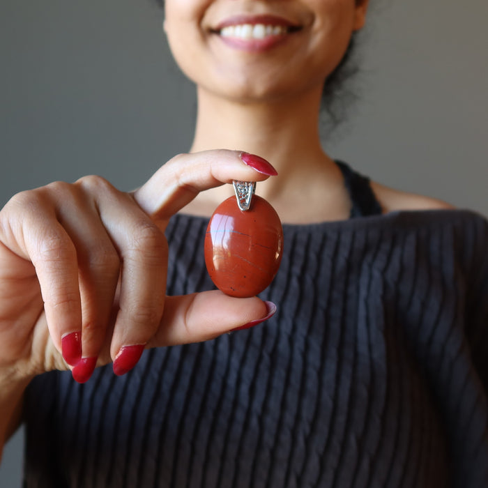 sheila of satin crystals holding red jasper pendant at her chest