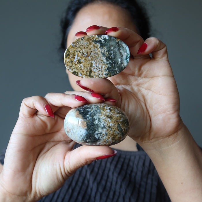 female holding two ocean jasper oval stones