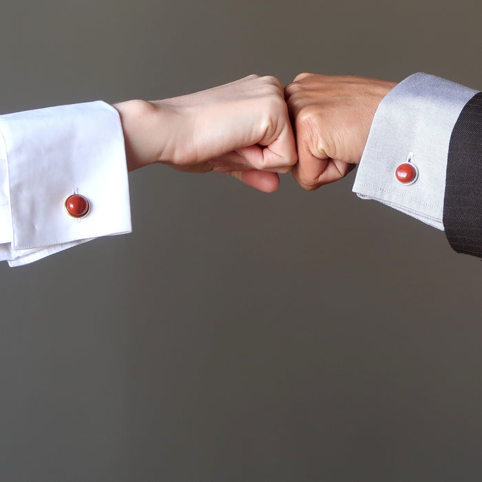 man and woman's hands fist bumping both wearing red jasper cufflinks on their french cuffs