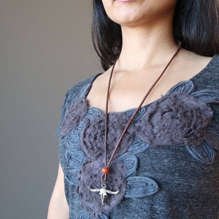 female wearing long silver jasper bull skull necklace