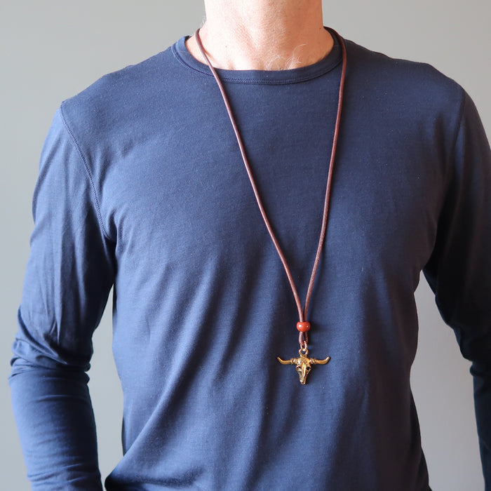 man wearing jasper bull skull necklace
