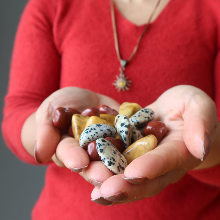 hands holding yellow, red, and dalmatian jasper tumbled stones