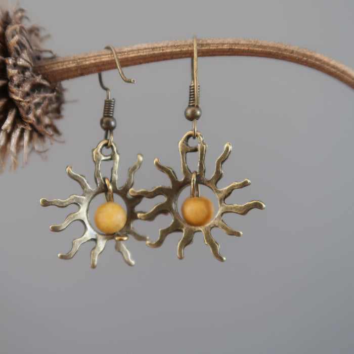 yellow jasper sun earrings hanging on a branch