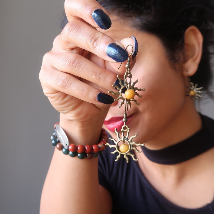 sheila of satin crystals holding stacked yellow jasper sun earrings