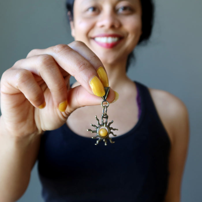 sheila of satin crystals holding a yellow jasper sun pendant