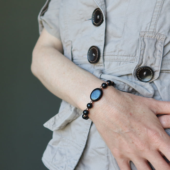 female hand wearing black jet stone and copper beaded bracelets
