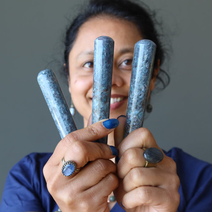 sheila of satin crystals holding up three blue kyanite massage wands