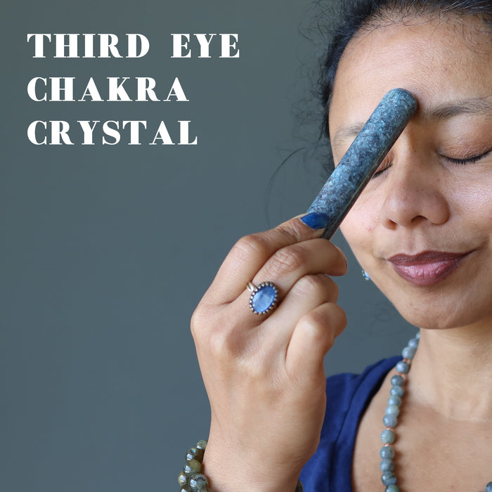 sheila of satin crystals holding up a blue kyanite massage wand to her third eye chakra