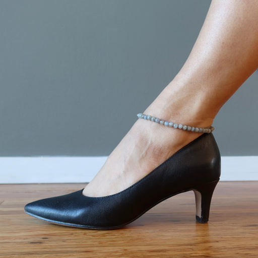 foot in black high heels wearing labradorite anklet