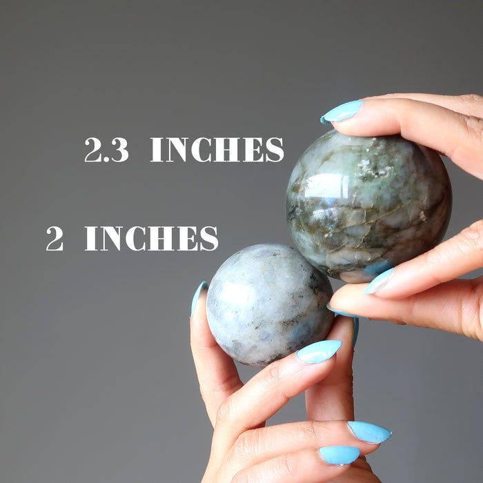 hand holding two labradorite spheres to compare size